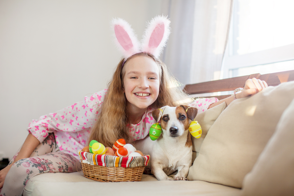 A girl on a couch with her dog and some Easter eggs in a basket