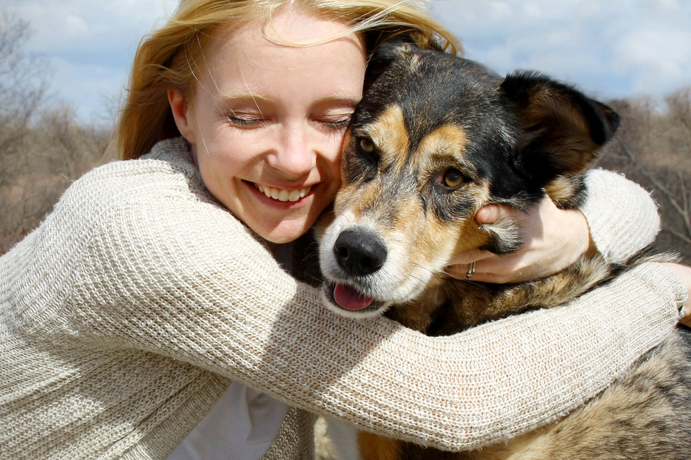 A woman hugging her adopted dog.