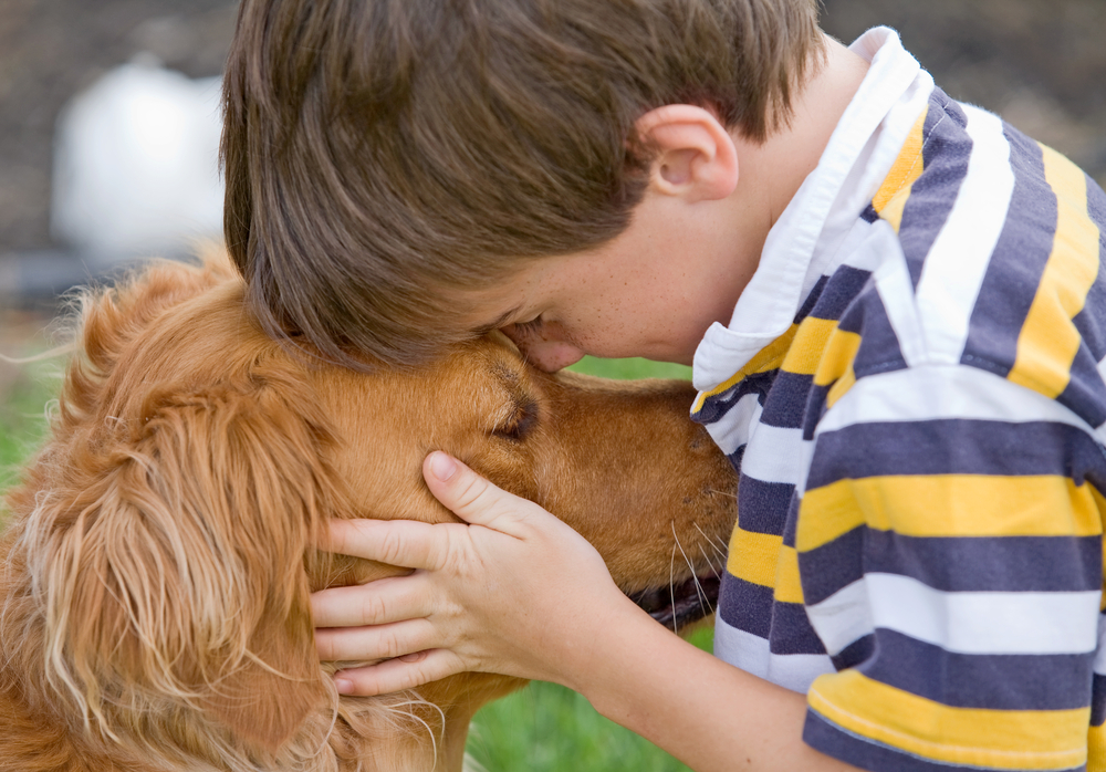 A boy cuddling with his golden retriever.