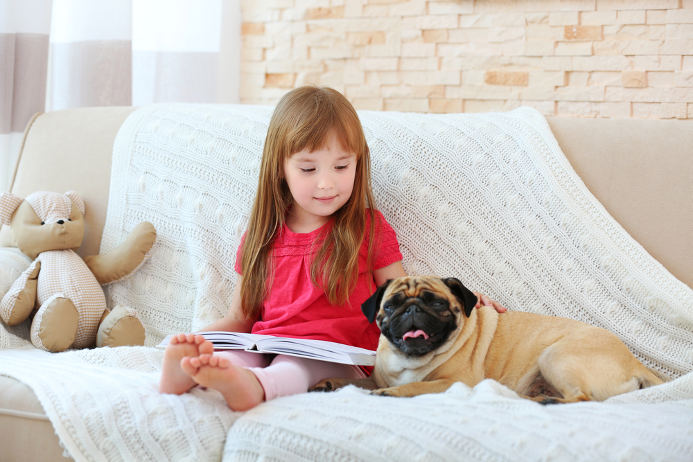 A child is reading to her dog