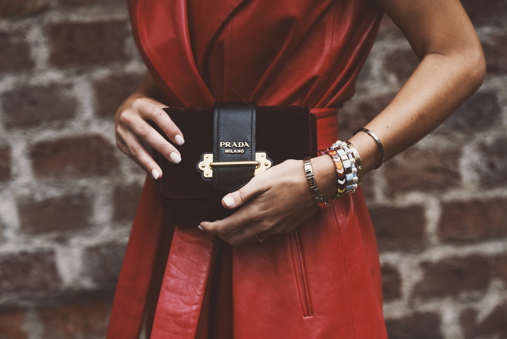 Well-dressed woman holding a Prada clutch