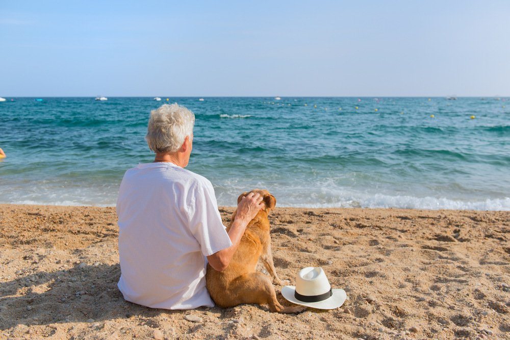 A senior citizen sitting on the beach with his dog.