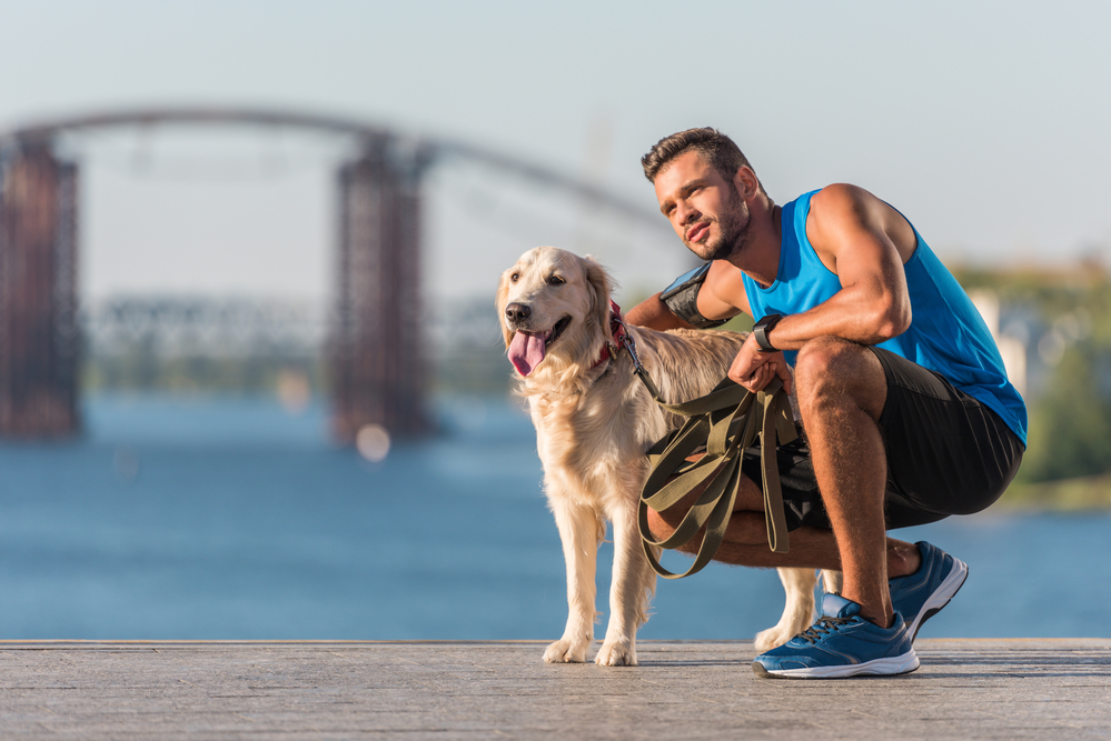 A man petting a dog after a run on the beach.